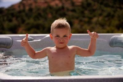 A young blonde boy is giving the thumbs up while in a hot tub outdoors.